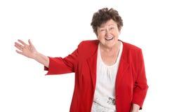 Donna più anziana isolata felice nella presentazione rossa con la mano immagine stock libera da diritti