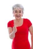 Donna più anziana potente e riuscita - pollici su isolati. Fotografie Stock