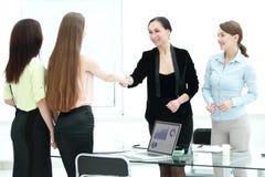 Donna più anziana soddisfatta e giovane handshake del responsabile dopo la firma del contratto in ufficio immagine stock