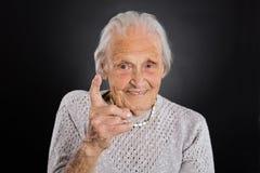 Donna più anziana sorridente che ondeggia il suo dito Fotografia Stock Libera da Diritti