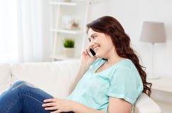 Donna più di dimensione che rivolge allo smartphone a casa Immagine Stock