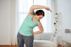 Donna più di dimensione che si esercita e che allunga a casa Fotografia Stock Libera da Diritti