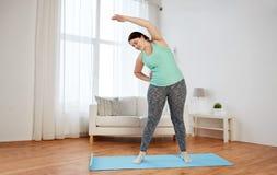 Donna più di dimensione che si esercita sulla stuoia a casa Immagine Stock Libera da Diritti