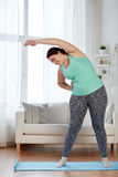 Donna più di dimensione che si esercita sulla stuoia a casa Immagini Stock
