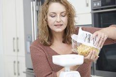 Donna più di dimensione sulla dieta che pesa pasta per il pasto Fotografie Stock Libere da Diritti