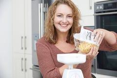Donna più di dimensione sulla dieta che pesa pasta per il pasto fotografia stock