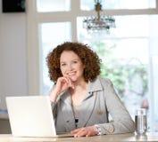 Donna più anziana attraente che per mezzo del computer portatile a casa Fotografia Stock