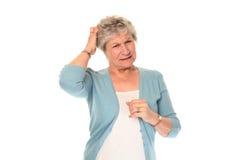 Donna più anziana maggiore che graffia testa Fotografia Stock Libera da Diritti