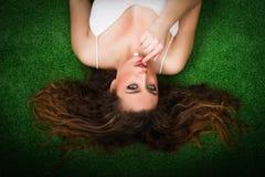 Donna piacevole che alletta sull'erba fotografia stock
