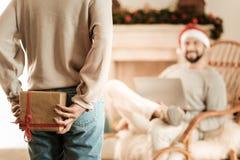 Donna piacevole piacevole che nasconde un regalo di Natale fotografia stock