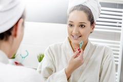 Donna piacevole che pulisce i suoi denti Immagini Stock