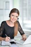 Donna piacevole di affari che si siede con il computer portatile Immagine Stock