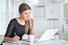 Donna piacevole di affari che si siede con il computer portatile Fotografia Stock Libera da Diritti