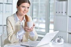 Donna piacevole di affari che si siede con il computer portatile Fotografia Stock