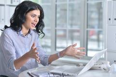 Donna piacevole di affari che si siede con il computer portatile Immagini Stock