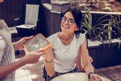 Donna piacevole felice che esamina la cameriera di bar fotografia stock