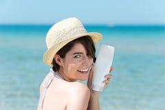 Donna piccola con una bottiglia della crema del sole Fotografie Stock
