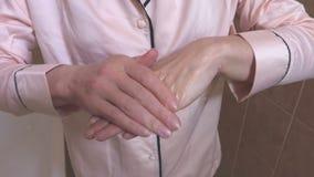Donna in pigiama che applica crema sulle mani archivi video