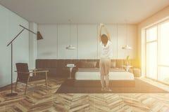 Donna in pigiami in camera da letto bianca illustrazione di stock