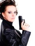 Donna in pistola di cuoio della holding di usura sopra bianco Fotografia Stock