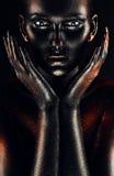 Donna in pittura nera con le mani intorno alle guance Immagine Stock