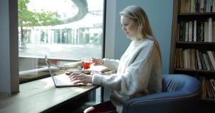 Donna in poltrona comoda facendo uso del computer portatile archivi video