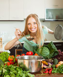 Donna positiva che cucina con la siviera dalle verdure crude Fotografie Stock Libere da Diritti