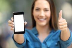 Donna positiva che mostra uno schermo in bianco dello Smart Phone Fotografia Stock