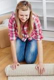 Donna positiva che rotola una moquette fuori Immagine Stock