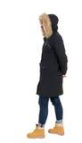 Donna posteriore di vista nel cercare del rivestimento di inverno Immagini Stock Libere da Diritti