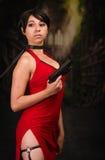 Donna potente sexy con un vestito rosso che tiene una pistola immagini stock