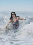 Donna praticante il surfing Immagini Stock