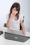 Donna premurosa al suo computer portatile Immagini Stock