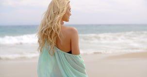 Donna premurosa in attrezzatura di estate alla spiaggia video d archivio