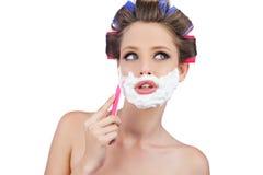 Donna premurosa in bigodini che posano con il rasoio Fotografia Stock