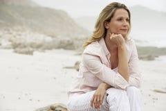 Donna premurosa che distoglie lo sguardo mentre sedendosi sulla roccia alla spiaggia Fotografia Stock Libera da Diritti