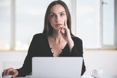 Donna premurosa che per mezzo del computer portatile Immagini Stock