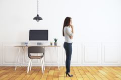 Donna premurosa nella sala con il posto di lavoro Immagine Stock