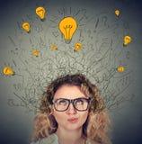 Donna premurosa in vetri con la testa di cui sopra di molte lampadine di idee Fotografia Stock Libera da Diritti