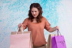 Donna preoccupata in blusa arancio che tiene la carta colourful di acquisto Fotografia Stock