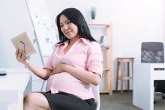 Donna preoccupata che abbraccia la sua pancia del bambino Immagini Stock