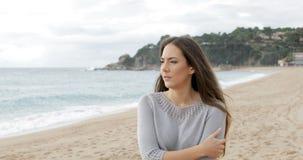 Donna preoccupata che cammina da solo sulla spiaggia video d archivio