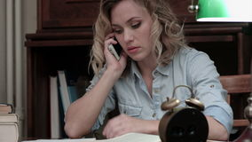 Donna preoccupata che parla sul telefono che si siede nel suo luogo di lavoro archivi video
