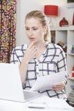 Donna preoccupata che per mezzo del computer portatile ed esaminando le finanze domestiche Immagine Stock Libera da Diritti