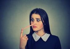 Donna preoccupata con il naso lungo Concetto del bugiardo fotografia stock