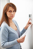 Donna preoccupata con il riscaldamento del Bill Turning Down Thermostat Fotografie Stock