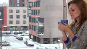 Donna preoccupata con il tè della tazza di caffè che si siede dalla finestra Caduta della neve dei fiocchi di neve stock footage