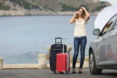 Donna preoccupata del viaggiatore che chiama assistenza con un'automobile di ripartizione Fotografia Stock