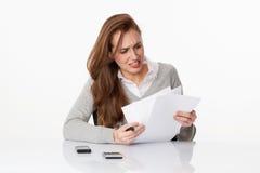 Donna preoccupata 20s che classifica i documenti amministrativi in ufficio Immagini Stock Libere da Diritti