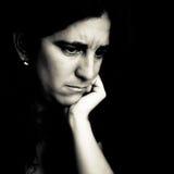 Donna preoccupata su una priorità bassa nera Immagine Stock